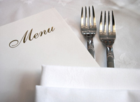 Dining table with food menu and silverware